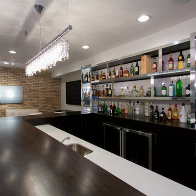 Example of a large trendy u-shaped dark wood floor seated home bar design in New York with glass countertops, white backsplash and black cabinets