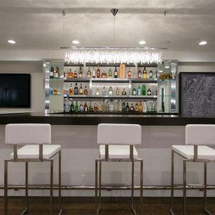 ニューヨークの広いコンテンポラリースタイルのおしゃれな着席型バー (コの字型、ガラスカウンター、白いキッチンパネル、濃色無垢フローリング、オープンシェルフ) の写真