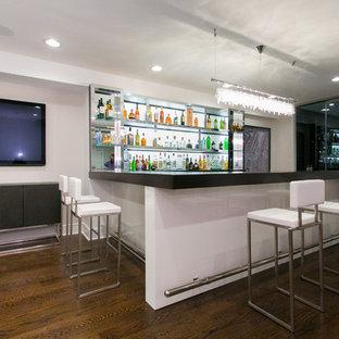 Esempio di un grande bancone bar design con parquet scuro, top in vetro, paraspruzzi bianco, pavimento marrone, top nero e nessun'anta