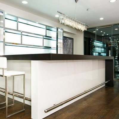 Large trendy u-shaped dark wood floor seated home bar photo in New York with glass countertops and white backsplash