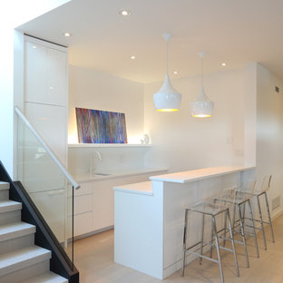 Design ideas for a medium sized contemporary u-shaped breakfast bar in Vancouver with a submerged sink, flat-panel cabinets, white cabinets, engineered stone countertops, white splashback, glass sheet splashback, light hardwood flooring and white worktops.