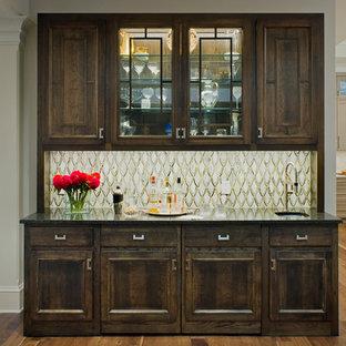 Foto di un grande angolo bar con lavandino tradizionale con pavimento in legno massello medio, lavello da incasso, ante con bugna sagomata, ante in legno bruno, top in laminato, paraspruzzi multicolore, pavimento marrone e top nero