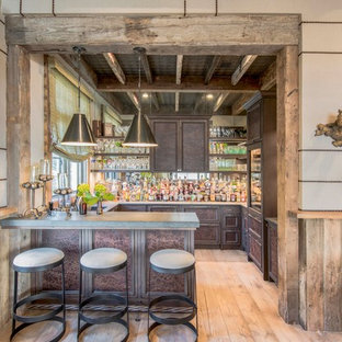 Foto di un grande bancone bar country con lavello sottopiano, ante con bugna sagomata, ante marroni, paraspruzzi a specchio, parquet chiaro e top grigio