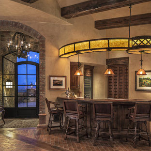 Example of a mid-sized southwest l-shaped brick floor and brown floor seated home bar design in Phoenix with medium tone wood cabinets and wood countertops