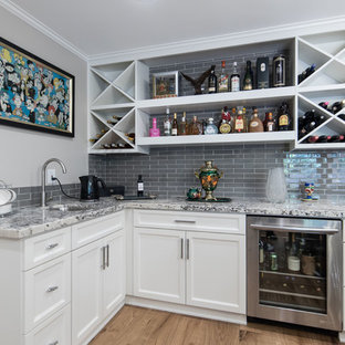 Example of a mid-sized transitional l-shaped medium tone wood floor and brown floor wet bar design in Los Angeles with an undermount sink, recessed-panel cabinets, white cabinets, gray backsplash, glass tile backsplash, gray countertops and granite countertops