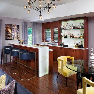 Foto di un grande bancone bar con lavello sottopiano, ante lisce, ante in legno scuro, top in onice, paraspruzzi giallo, paraspruzzi in lastra di pietra, pavimento in legno massello medio e top giallo