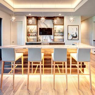 ダラスのコンテンポラリースタイルのおしゃれな着席型バー (ll型、フラットパネル扉のキャビネット、濃色木目調キャビネット、白いキッチンパネル、淡色無垢フローリング、ベージュの床、白いキッチンカウンター) の写真