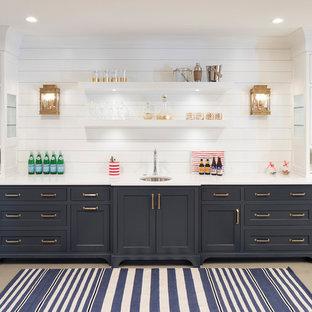 ミネアポリスのビーチスタイルのおしゃれなウェット バー (I型、アンダーカウンターシンク、シェーカースタイル扉のキャビネット、青いキャビネット、白いキッチンパネル、木材のキッチンパネル、グレーの床、白いキッチンカウンター、コンクリートの床) の写真