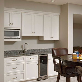 Medium sized classic single-wall wet bar in DC Metro with a submerged sink, shaker cabinets, white cabinets, granite worktops, ceramic flooring and beige floors.