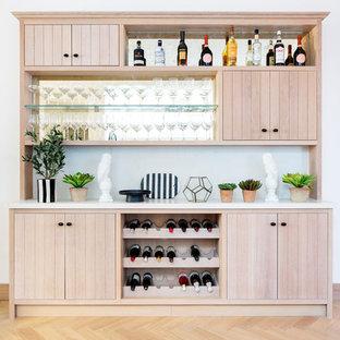 ロンドンのモダンスタイルのおしゃれなホームバー (I型、シンクなし、ルーバー扉のキャビネット、淡色木目調キャビネット、ミラータイルのキッチンパネル、淡色無垢フローリング、ベージュの床、白いキッチンカウンター) の写真