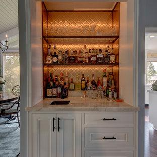 Maritim inredning av en mellanstor linjär hemmabar med vask, med en undermonterad diskho, luckor med infälld panel, vita skåp, bänkskiva i kvartsit, brunt stänkskydd, stänkskydd i glaskakel och mörkt trägolv
