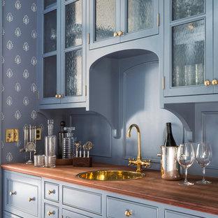Immagine di un armadio bar classico di medie dimensioni con lavello da incasso, ante di vetro, ante blu, top in legno, paraspruzzi blu e top marrone