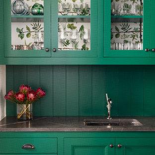 オースティンの広いトランジショナルスタイルのおしゃれなウェット バー (I型、緑のキャビネット、アンダーカウンターシンク、ガラス扉のキャビネット、緑のキッチンパネル、木材のキッチンパネル、グレーのキッチンカウンター) の写真