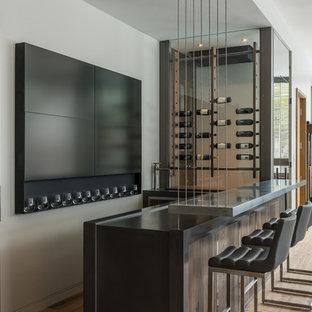Idee per un piccolo bancone bar rustico con top in acciaio inossidabile, parquet chiaro, pavimento beige e top grigio