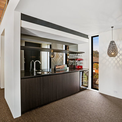 Small trendy carpeted home bar photo in Central Coast with an undermount sink, flat-panel cabinets, dark wood cabinets, solid surface countertops, black backsplash, mirror backsplash and black countertops