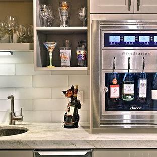 Esempio di un piccolo angolo bar con lavandino classico con lavello sottopiano, ante in stile shaker, ante beige, top in pietra calcarea, paraspruzzi bianco, paraspruzzi con piastrelle di vetro, parquet scuro e pavimento marrone