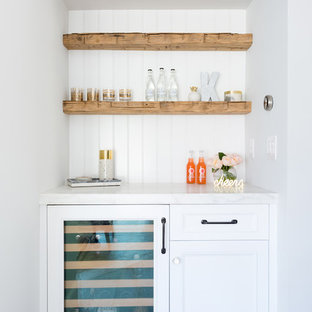 Design ideas for a small traditional single-wall wet bar in Orange County with no sink, white cabinets, marble worktops, white splashback, wood splashback, light hardwood flooring, white worktops and recessed-panel cabinets.