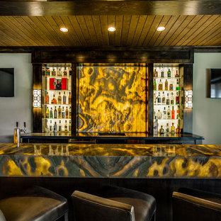 Cette photo montre un très grand bar de salon tendance en U avec des tabourets, un évier encastré, un placard sans porte, des portes de placard en bois sombre, un plan de travail en onyx, une crédence jaune, une crédence en dalle de pierre et un sol en bois foncé.