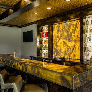 ダラスのコンテンポラリースタイルのおしゃれな着席型バー (アンダーカウンターシンク、オープンシェルフ、オニキスカウンター、黄色いキッチンパネル、石スラブのキッチンパネル、濃色無垢フローリング、黄色いキッチンカウンター) の写真