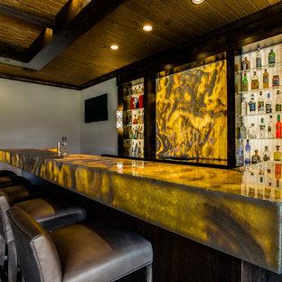 Idee per un ampio bancone bar minimal con lavello sottopiano, nessun'anta, ante in legno bruno, top in onice, paraspruzzi giallo, paraspruzzi in lastra di pietra e parquet scuro