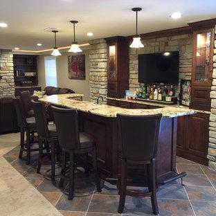 Foto di un grande bancone bar american style con pavimento con piastrelle in ceramica, ante con bugna sagomata, top in granito, paraspruzzi beige, paraspruzzi con piastrelle in pietra, pavimento multicolore e ante in legno bruno