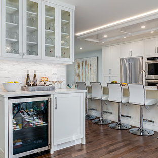 Cette photo montre un très grand bar de salon linéaire chic avec un placard à porte shaker, des portes de placard blanches, un plan de travail en granite, une crédence grise, une crédence en carreau de céramique et un sol en bois brun.