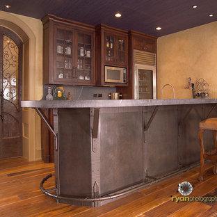 Foto di un bancone bar boho chic di medie dimensioni con ante in stile shaker, ante in legno bruno, top in saponaria e pavimento in legno massello medio