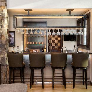 Foto di un piccolo bancone bar stile rurale con lavello sottopiano, top in acciaio inossidabile e pavimento in legno massello medio