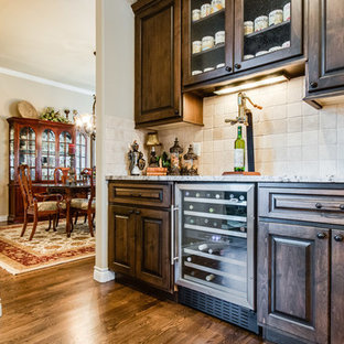 This is an example of a small rustic single-wall wet bar in Denver with raised-panel cabinets, dark wood cabinets, marble worktops, beige splashback, terracotta splashback and medium hardwood flooring.