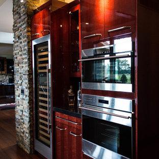 Immagine di un grande angolo bar minimal con ante lisce, top in granito, paraspruzzi nero, pavimento in bambù e pavimento marrone