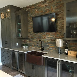Photo of a rustic wet bar in Cleveland with a submerged sink, glass-front cabinets, dark wood cabinets, multi-coloured splashback, stone tiled splashback, dark hardwood flooring and marble worktops.