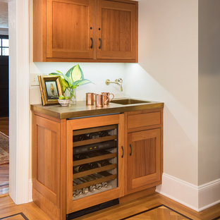 Example of a small classic l-shaped multicolored floor and light wood floor home bar design in New York with shaker cabinets, brown cabinets, marble countertops, green backsplash and an integrated sink