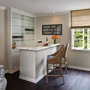 Example of a small transitional l-shaped dark wood floor and brown floor seated home bar design in Los Angeles with recessed-panel cabinets, white cabinets and white countertops