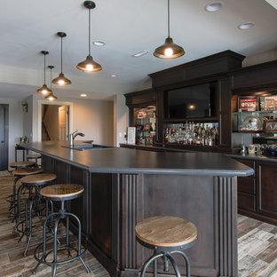 Esempio di un grande angolo bar con lavandino country con lavello da incasso, ante con riquadro incassato, ante in legno bruno, paraspruzzi con lastra di vetro, pavimento con piastrelle in ceramica, pavimento multicolore, top grigio e top in laminato