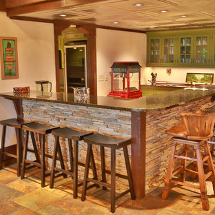 Example of a large mountain style l-shaped slate floor seated home bar design in Other with glass-front cabinets, green cabinets and granite countertops
