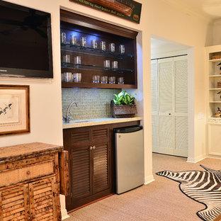 ヒューストンの広いトラディショナルスタイルのおしゃれな着席型バー (ll型、ルーバー扉のキャビネット、濃色木目調キャビネット、人工大理石カウンター、グレーのキッチンパネル、ガラスタイルのキッチンパネル、淡色無垢フローリング) の写真