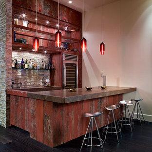 Esempio di un grande bancone bar industriale con ante con finitura invecchiata, paraspruzzi multicolore, parquet scuro e pavimento nero