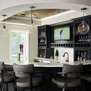 ミネアポリスの広いトランジショナルスタイルのおしゃれな着席型バー (黒いキャビネット、クオーツストーンカウンター、白いキッチンパネル、サブウェイタイルのキッチンパネル、ガラス扉のキャビネット) の写真