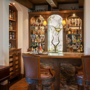 Foto di un piccolo bancone bar stile rurale con ante con riquadro incassato, top in quarzite, ante in legno scuro, paraspruzzi a specchio, pavimento in terracotta e pavimento rosso