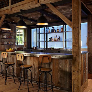 Example of a country u-shaped medium tone wood floor and beige floor home bar design in New York with dark wood cabinets