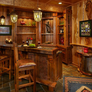 Example of a large mountain style u-shaped slate floor seated home bar design in Other with recessed-panel cabinets and dark wood cabinets
