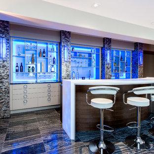 カルガリーの大きいコンテンポラリースタイルのおしゃれな着席型バー (ll型、フラットパネル扉のキャビネット、白いキャビネット、磁器タイルの床、黒い床、オニキスカウンター) の写真