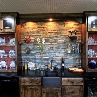 ミネアポリスの中くらいのトランジショナルスタイルのおしゃれな着席型バー (アンダーカウンターシンク、シェーカースタイル扉のキャビネット、濃色木目調キャビネット、マルチカラーのキッチンパネル、スレートのキッチンパネル、スレートの床、茶色い床) の写真