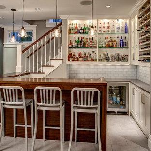 Ejemplo de bar en casa con barra de bar en U, de estilo americano, grande, con armarios estilo shaker, puertas de armario blancas, salpicadero blanco, salpicadero de azulejos de vidrio y suelo gris