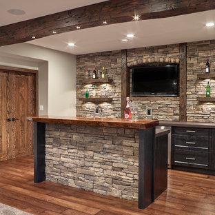 他の地域の広いおしゃれなウェット バー (ll型、アンダーカウンターシンク、シェーカースタイル扉のキャビネット、濃色木目調キャビネット、木材カウンター、グレーのキッチンパネル、石スラブのキッチンパネル、ラミネートの床、茶色い床、茶色いキッチンカウンター) の写真
