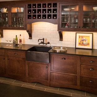 Foto di un piccolo armadio bar american style con lavello da incasso, ante a filo, ante marroni, top in saponaria, paraspruzzi bianco, paraspruzzi con piastrelle in ceramica, pavimento in legno massello medio, pavimento marrone e top nero