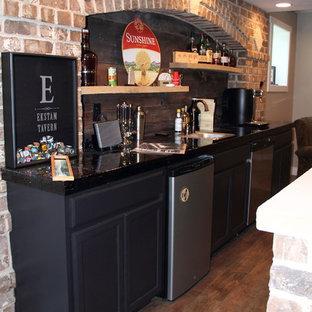 他の地域の中くらいのラスティックスタイルのおしゃれなウェット バー (ll型、アンダーカウンターシンク、落し込みパネル扉のキャビネット、黒いキャビネット、ライムストーンカウンター、茶色いキッチンパネル、石タイルのキッチンパネル、セラミックタイルの床) の写真