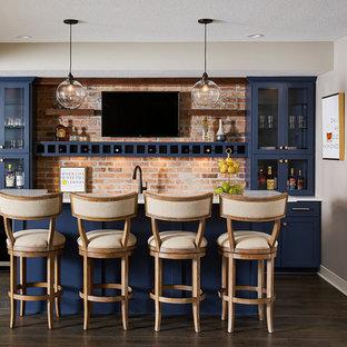 ミネアポリスの中くらいのトランジショナルスタイルのおしゃれなウェット バー (ll型、アンダーカウンターシンク、青いキャビネット、珪岩カウンター、レンガのキッチンパネル、クッションフロア、茶色い床、白いキッチンカウンター、ガラス扉のキャビネット、オレンジのキッチンパネル) の写真