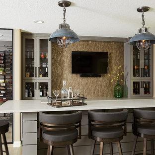 ミネアポリスの中くらいのトランジショナルスタイルのおしゃれな着席型バー (グレーのキャビネット、珪岩カウンター、淡色無垢フローリング、ガラス扉のキャビネット、ベージュキッチンパネル、ベージュの床) の写真