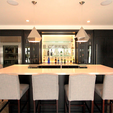 Basement Bar with Island Featuring Bar Height Seating and Undermount Sink
